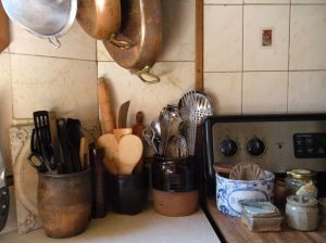 old redware holding utensils next to the stove. . .