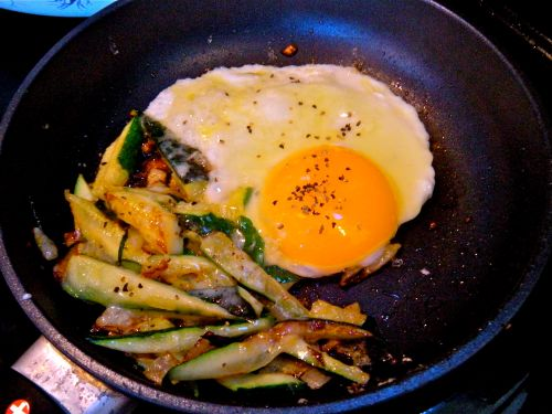 zucchini & onion in olive oil w/cheddar cheese beside a jumbo organic egg for a hi protein breakfast!